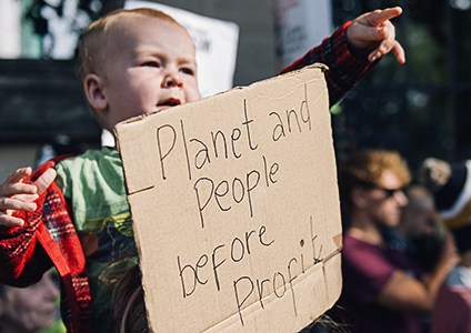 "A baby seems to raise his arms in protest as he sits on his father's shoulders, seen behind a poster reading ""people and planet before profit"""