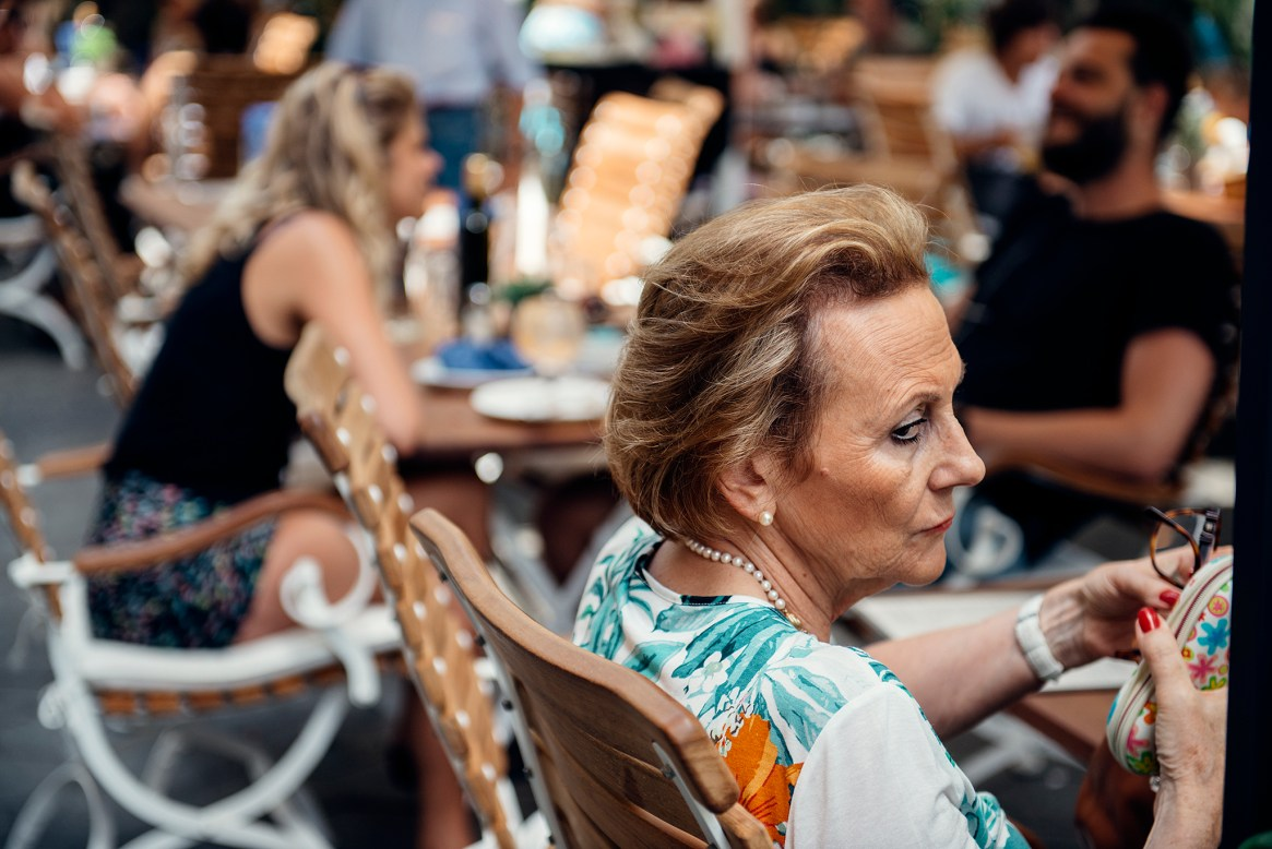 A styllish, wealthy looking older woman wears a serious expression as she dines al fresco at a cafe on the Passeig de Gràcia, Barcelona