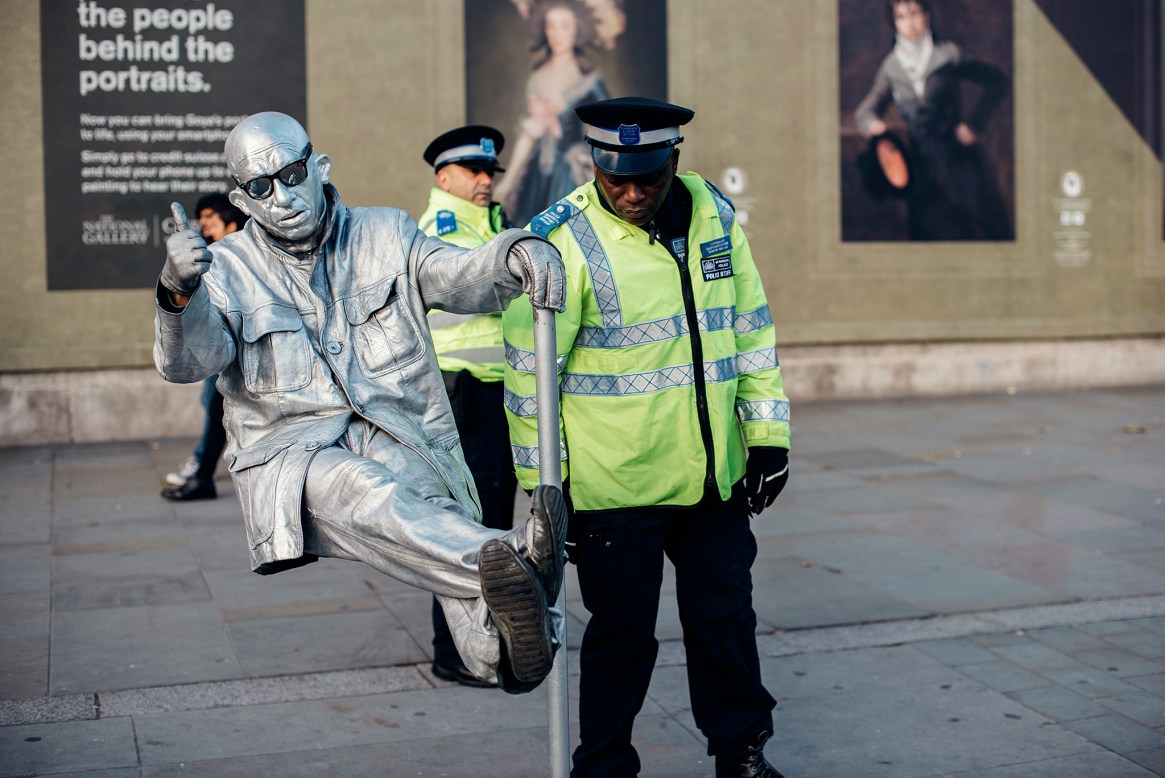 Two uniformed Metropolitan Police community support officers focus their attention on a street entertainer dressed head to toe in silver, in front of a billboard advertising a Goya exhibition outside the National Gallery on Trafalgar Square in London.
