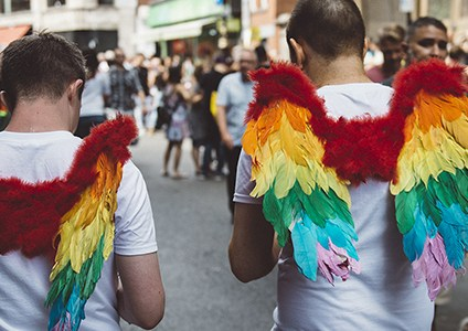 Two mean wearing rainbow-coloured angel wings walk the streets at London Pride 2018