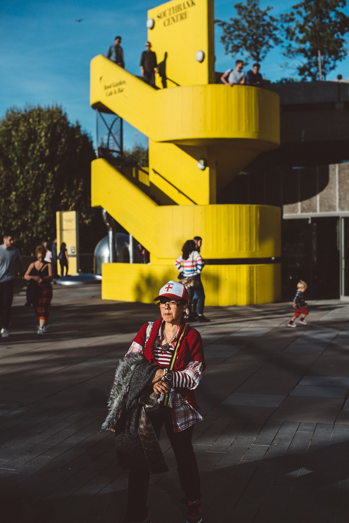A woman wearing red and white walks past a bright yellow staircase at sunset on the South Bank in London