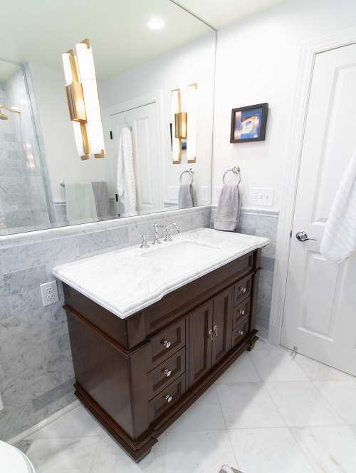 Dark wood vanity with white counter top and large mirror
