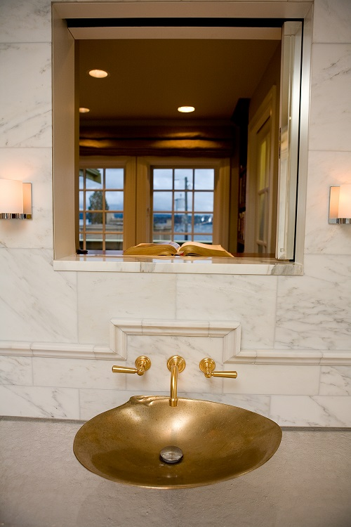 Above counter gold sink with white marble backsplash