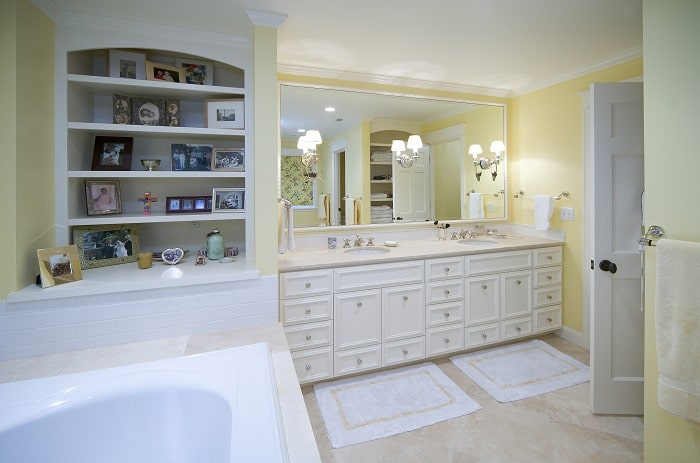 white cabinet vanity with large mirror above and light yellow walls