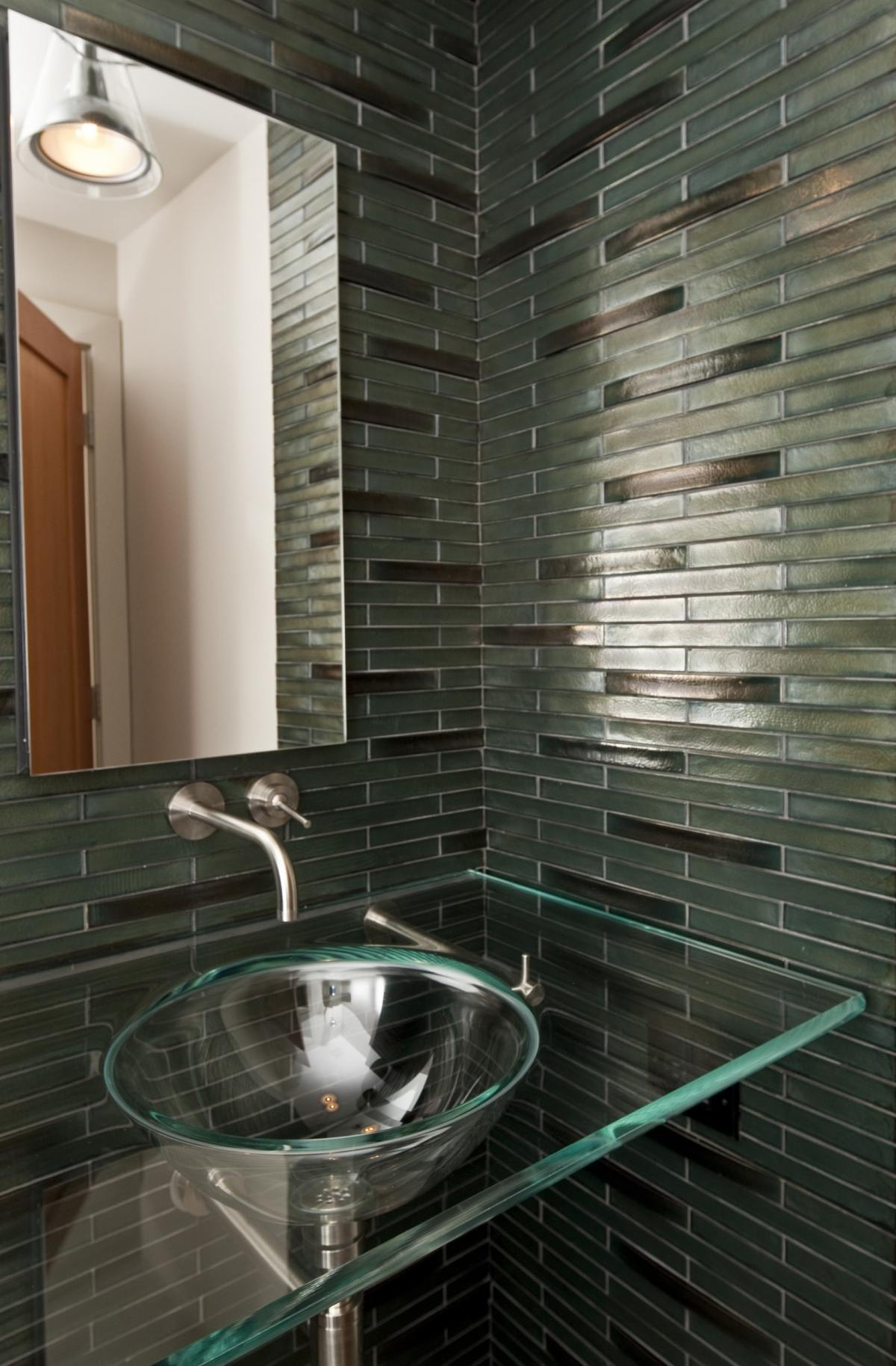 Clear glass above sink on clear glass counter top with dark green tile backsplash