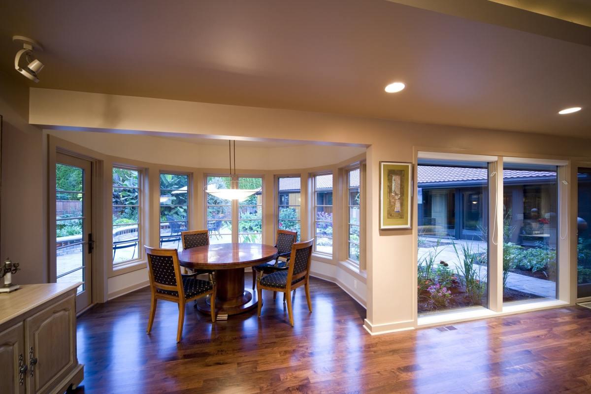 dinning room set inside of a partial hexagon room of windows