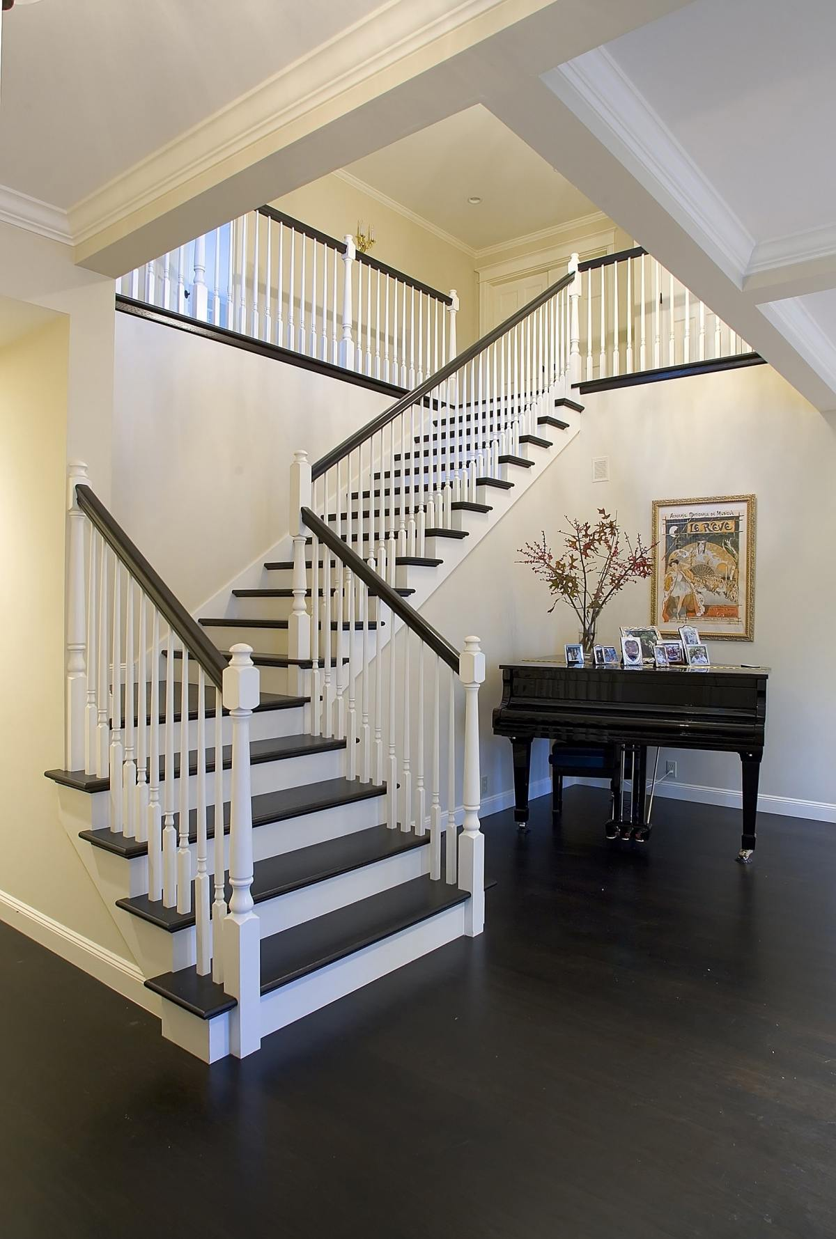 white corner staircase with black wood steps and black handrail going up around a black grand piano