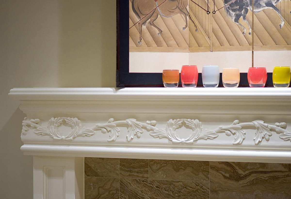 multiple colorful candle glasses on a decorative white mantel place