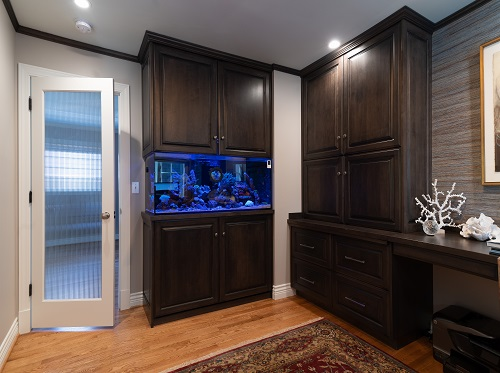 Dark cabinets around blue fish tank and glass door
