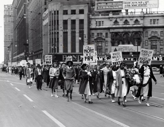 Members of the UAW Women's Auxiliary march down Woodward Ave. and carry signs that denounce U.S. involvement in the Second World War and low worker wages, Detroit, Michigan.