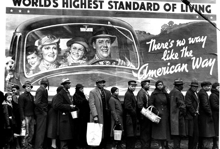 African American flood victims lined up to get food & clothing fr. Red Cross relief station in front of billboard extolling WORLD'S HIGHEST STANDARD OF LIVING/ THERE'S NO WAY LIKE THE AMERICAN WAY. City: LOUISVILLE State: KY Country: US Photographer: MARGARET BOURKE-WHITE/TimePix