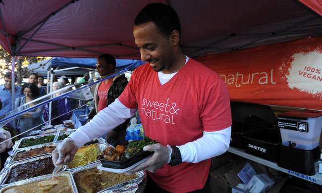 David Wilson, one of the owners of Sweet & Natural, a vegan cafe and bakeshop in Mt. Rainier, prepares orders for people in line at his booth at the Vegan SoulFest.