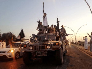 In this June 23, 2014, file photo, fighters from the Islamic State group parade in a commandeered Iraqi security forces armored vehicle down a main road at the northern city of Mosul, Iraq. (AP Photo/File)