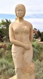 Light beige stone statue of the Greek Goddess Lucinda. Lucinda stands 10 feet tall, hair tied back around face, flat facial features, Greek woman's gown with one arm in front and one arm behind. Background Is a blue sky with New Mexico natural landscape and bushes.