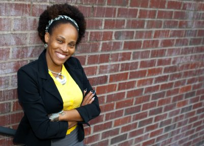 Image of Mari Galloway standing in front of a brick wall smiling.