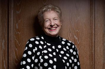 Image of Stephanie Shirley smiling in front of a wooden door.