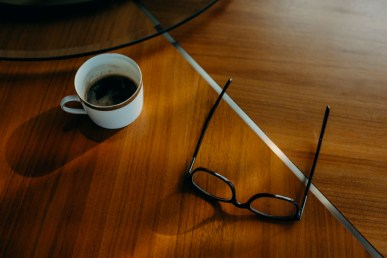 an ambient photograph of a cup of coffee and pair of spectacles on a wooden table