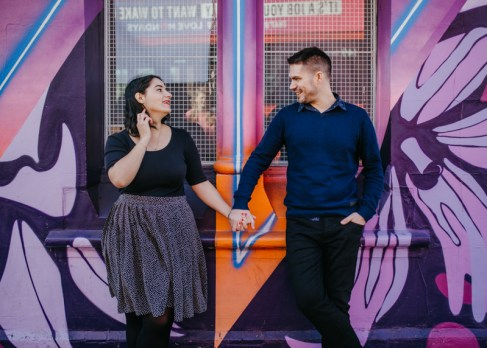 A couple holding hands in front of a colourful backdrop