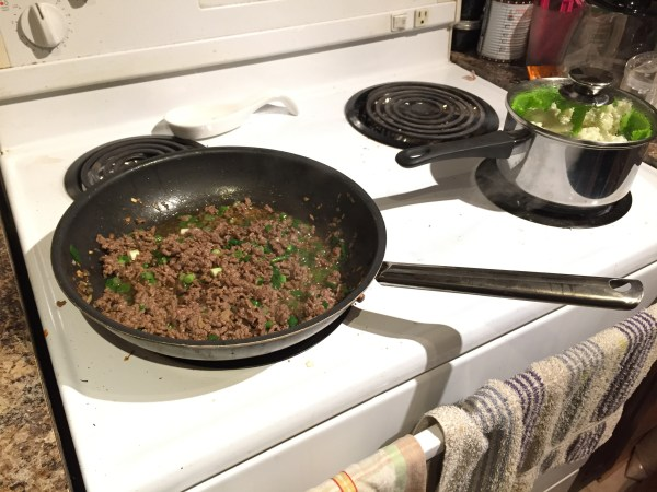 cook ground beef in pan with spices and green onions