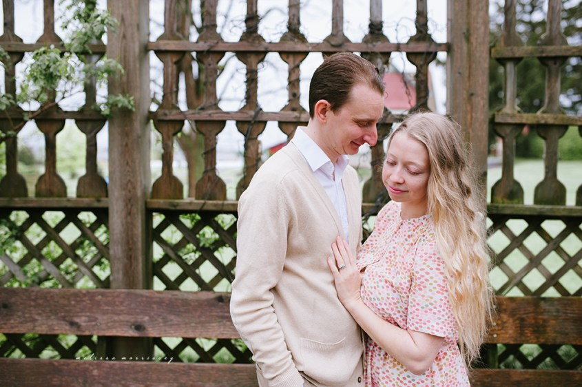 stephanie de montigny white cherry blossoms, arboretum, experimental farm ornamental gardens, ottawa melissa morrissey photography engagement photos, bride, blue eyes, curly blonde hair, stunning pink polka dot vintage dress, natural cardigan, hugging