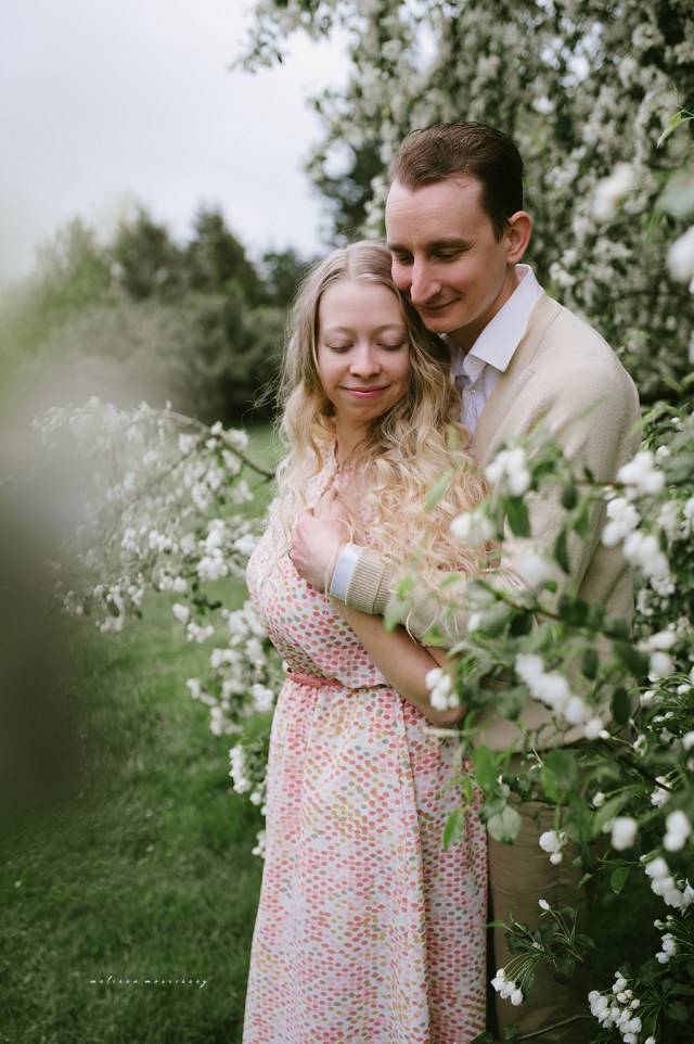 stephanie de montigny white cherry blossoms photos ottawa melissa morrissey photography fiance hugging bride, curly blonde hair, stunning pink vintage dress, natural cardigan with elbow patches