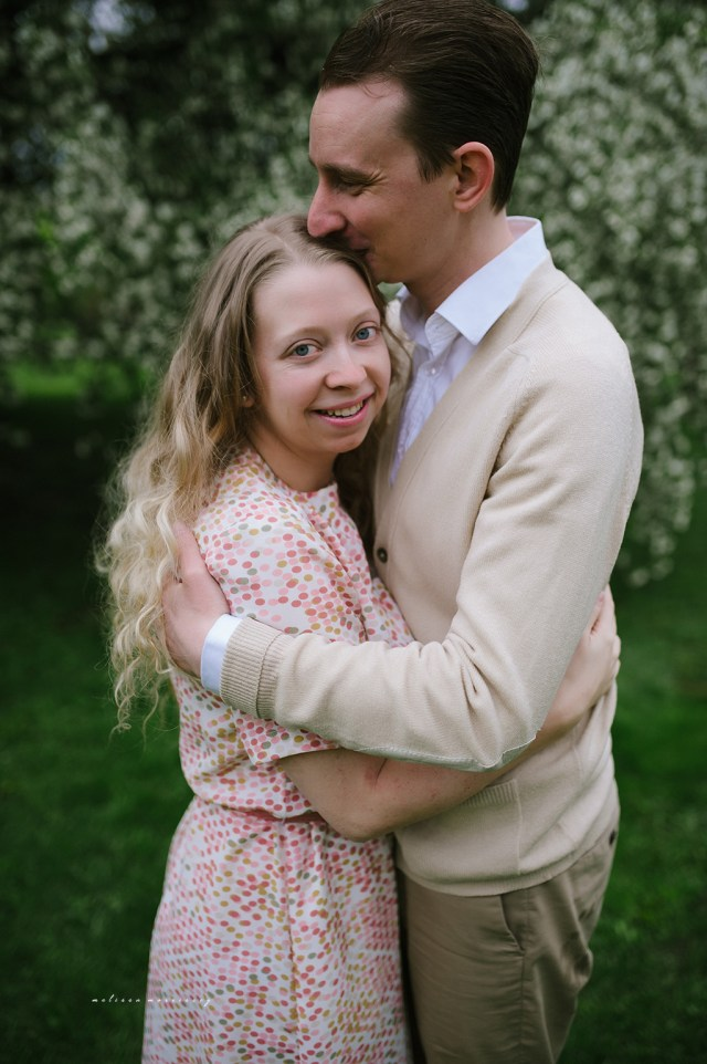stephanie de montigny cherry blossoms photos ottawa melissa morrissey photography fiance kissing her forehead as she smiles at the camera with her blue eyes, curly blonde hair, and stunning pink vintage dress