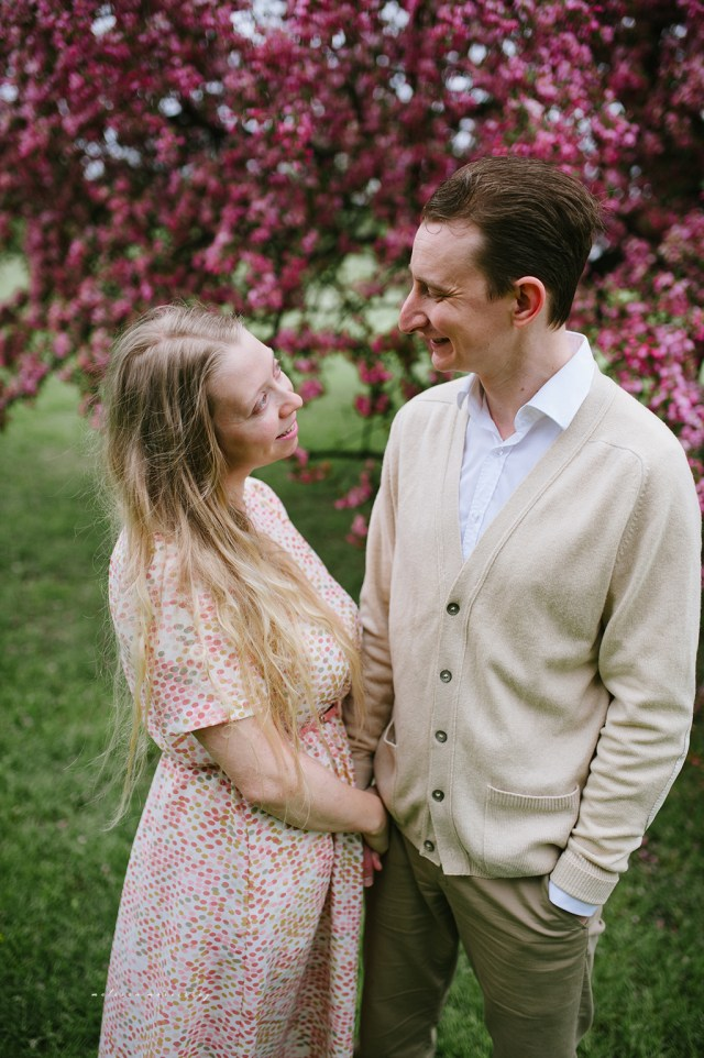 stephanie de montigny pink cherry blossoms photos ottawa melissa morrissey photography engagement photos, bride, blue eyes, curly blonde hair, stunning pink polka dot vintage dress, groom smiling natural cardigan leather elbow patches