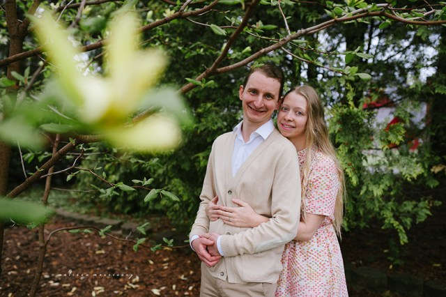 stephanie de montigny arboretum ottawa, magnolias, melissa morrissey photography, engagement photos, bride, blue eyes, curly blonde hair, stunning pink polka dot vintage dress, groom smiling natural cardigan leather elbow patches, hugging lovingly, smiling