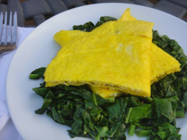 Omelet over cooked collard greens