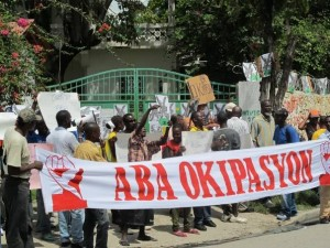Haitian demonstrators, their banner says Down with occupation