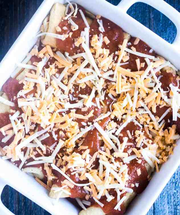 Enchildas in a white casserole dish sprinkled with cheese prior to baking them.