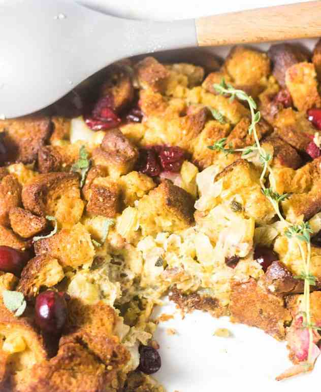 Gluten Free Cranberry Stuffing in a casserole dish garnished with fresh thyme.
