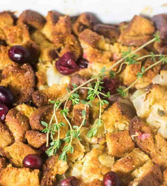 Gluten Free Cranberry Stuffing in a casserole dish and garnished with fresh thyme.