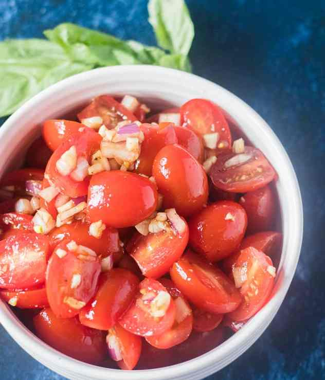 Fresh cherry tomatoes mixed with garlic, red onion, olive oil and balsamic vinegar in a bowl.