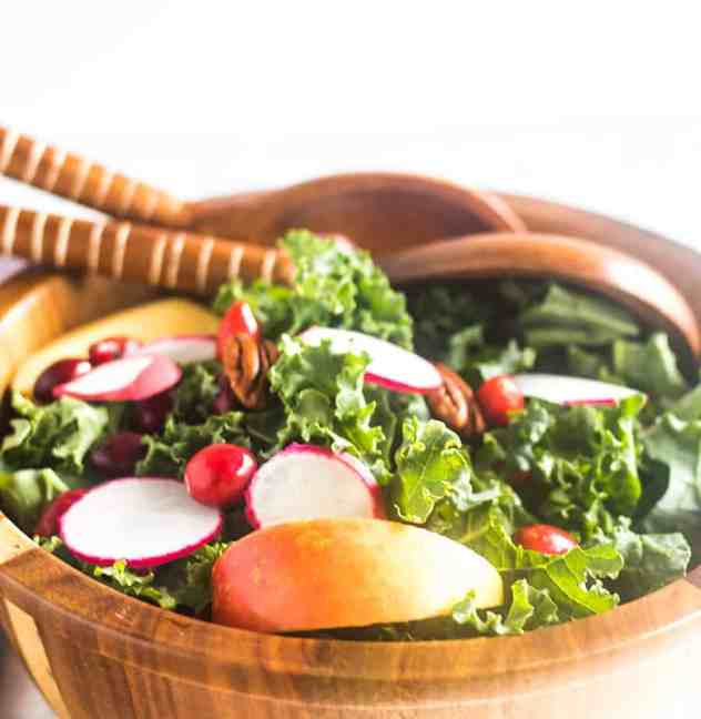 Apple Cranberry Kale Salad in wooden salad b.owl with serving spoons