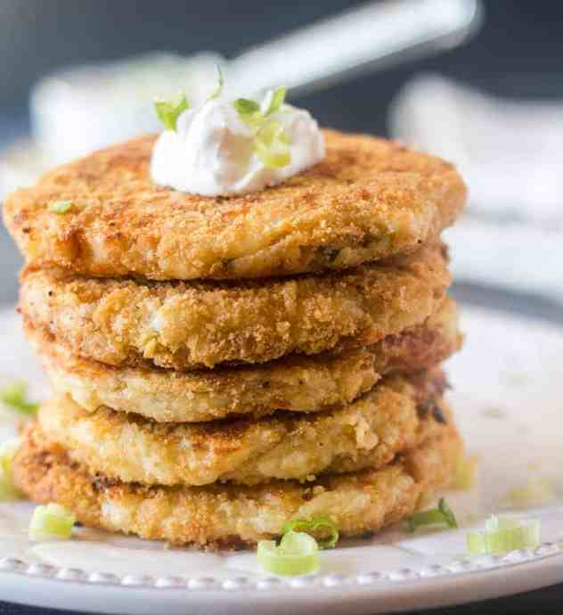 Mashed Potato Cakes stacked on a white plate topped with sour cream & green onions.