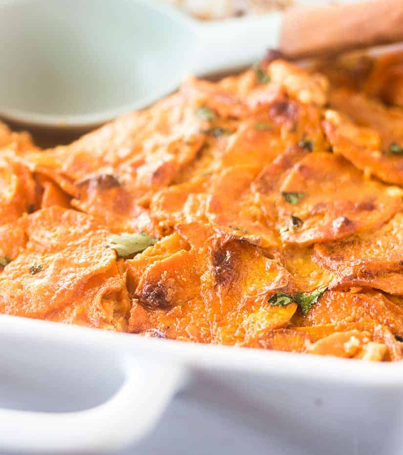 Spicy Scalloped Sweet Potatoes in a white casserole dish.