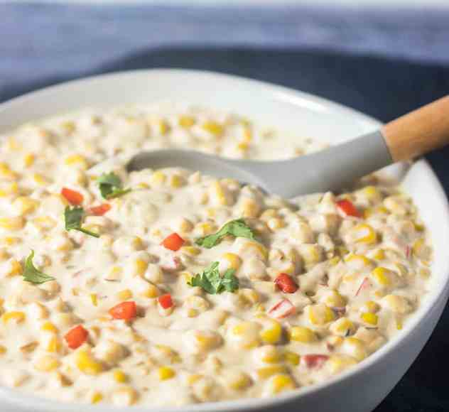 Creamed Corn garnished with red bell pepper and parsley.