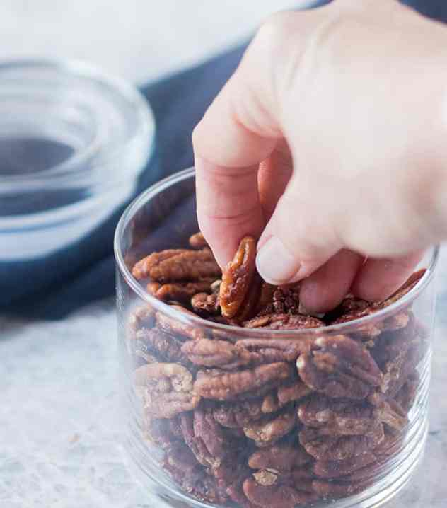 Hand reaching into a jar full of Maple Cinnamon Roasted Pecans.