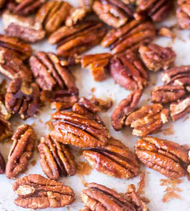 Maple Cinnamon Roasted Pecans on a sheet pan with parchment paper.
