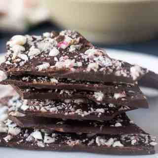 Dark Chocolate Peppermint Bark with crushed candy canes stacked on a plate.