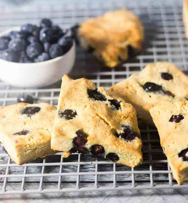 Blueberry Scones on a cooling rack and bowl of blueberries.