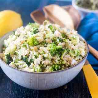 Broccoli Quinoa Salad in a bowl with some wooden salad spoons and a lemon.