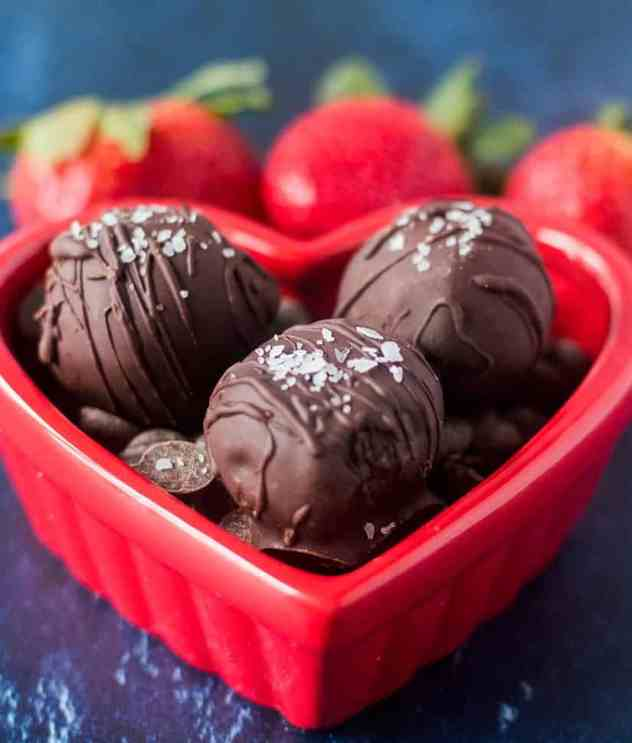 Double Chocolate Truffles in a red heart shaped bowl with some strawberries in the background.