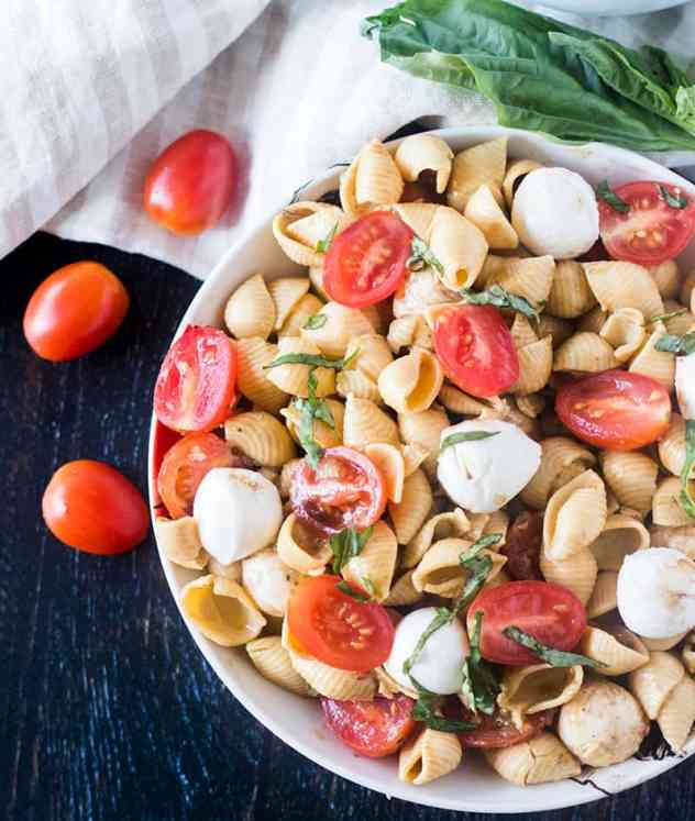 Caprese Pasta Salad in a white bowl with grape tomatoes beside it.