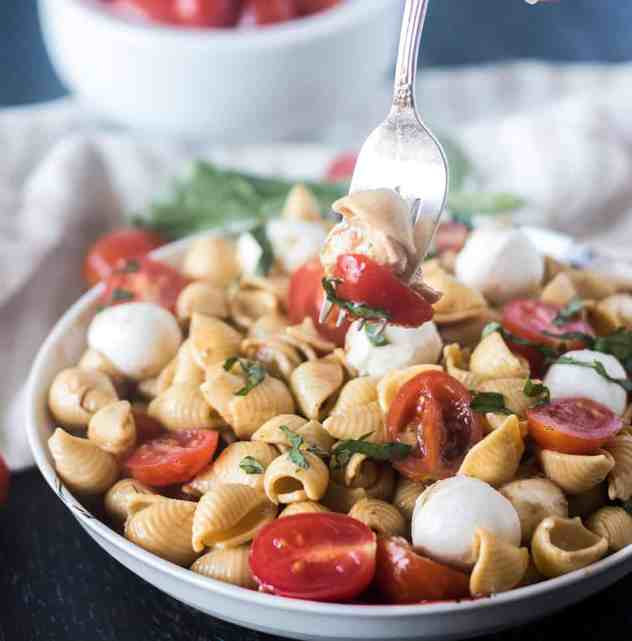 Caprese Pasta Salad in a white bowl and some on a fork.