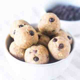 Chickpea Cookie Dough Bites in a white bowl in a white bowl with a bowl of chocolate chips in the background.