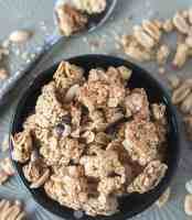 Peanut Butter Granola Clusters in a black bowl with a spoon beside it.