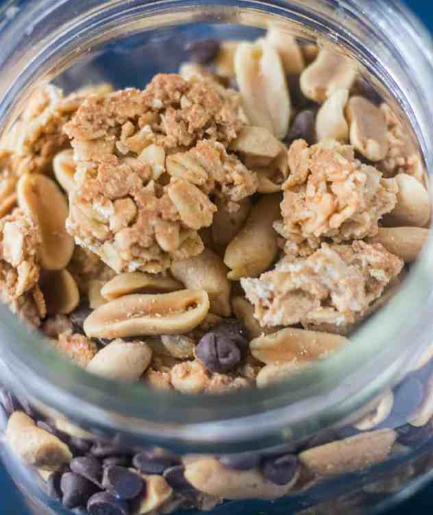 Peanut Butter Granola in a glass jar with peanuts and mini chocolate chips.