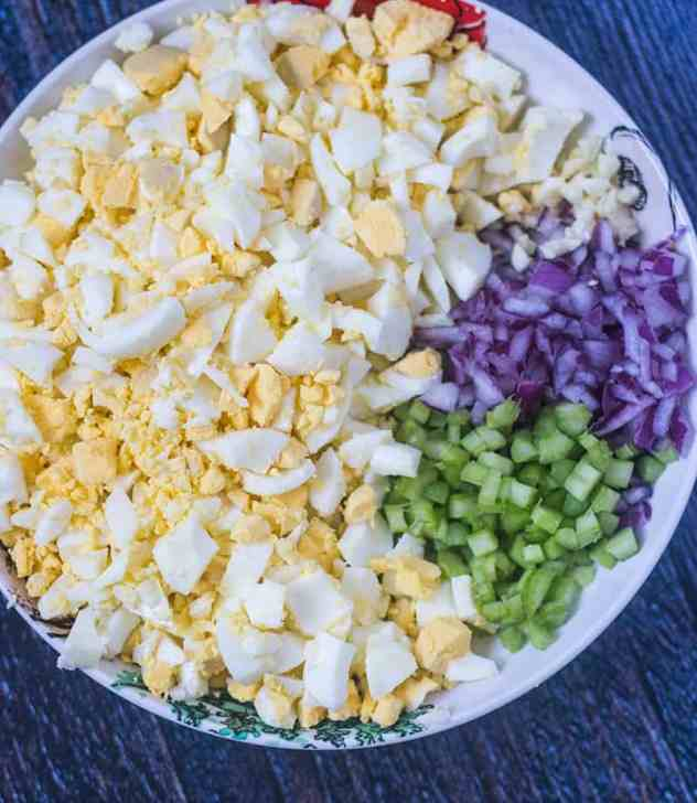 Chopped Hard boiled eggs, diced red onion, diced celery, and minced garlic in a bowl.